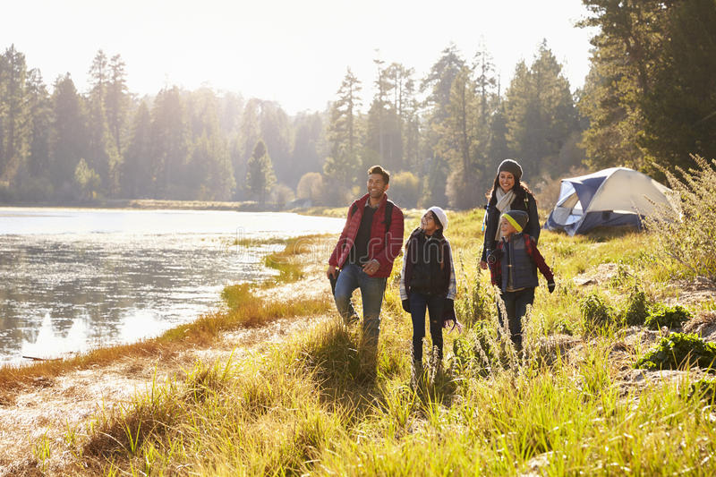 Parents and two children on camping trip walking near a lake stock photo