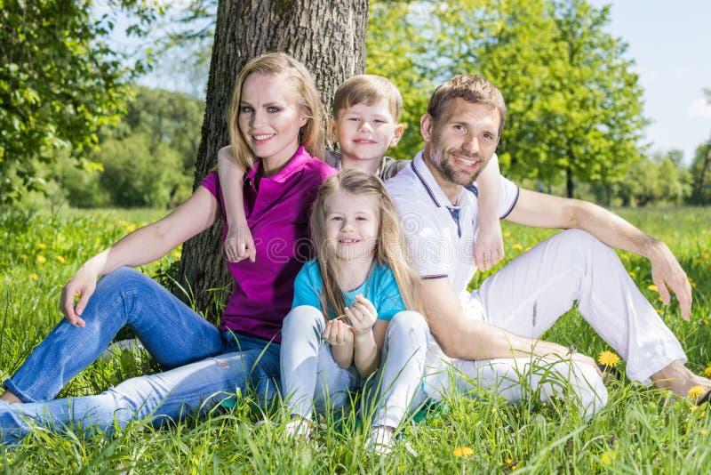 Family sitting under the tree stock photos