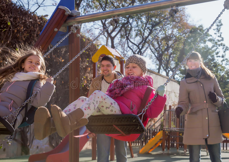 Parents and two daughters at playground royalty free stock photos