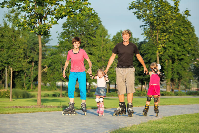 Parents and two daughters skating stock photography
