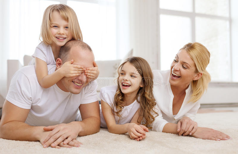 Parents and two girls lying on floor at home royalty free stock images