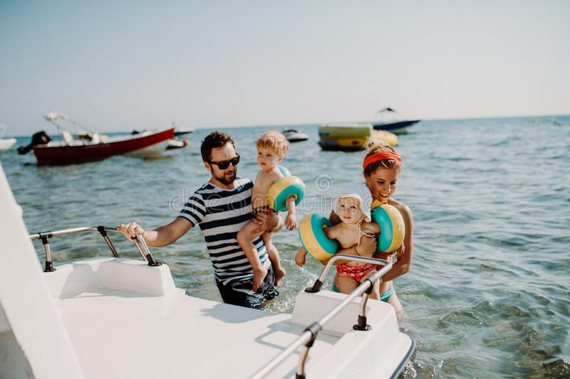 Parents with two small toddler children standing by boat on summer holiday. stock image