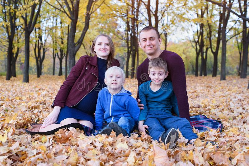 Parents and two sons relax and chat in the park. Pregnant mom Happy family. Yellow autumn foliage, sunny day royalty free stock images