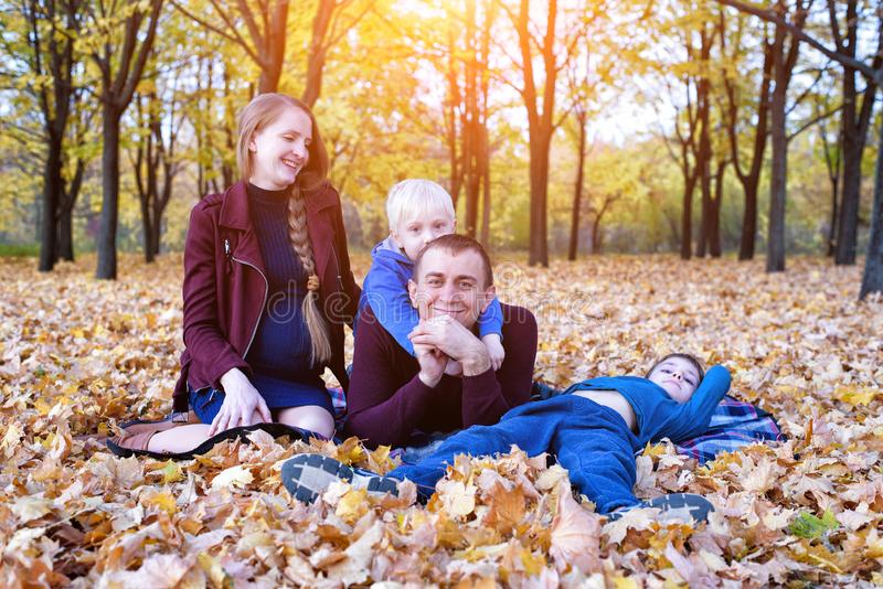 Parents and two sons relax and chat in the park. Pregnant mom Happy family. Yellow autumn foliage, sunny day royalty free stock photos