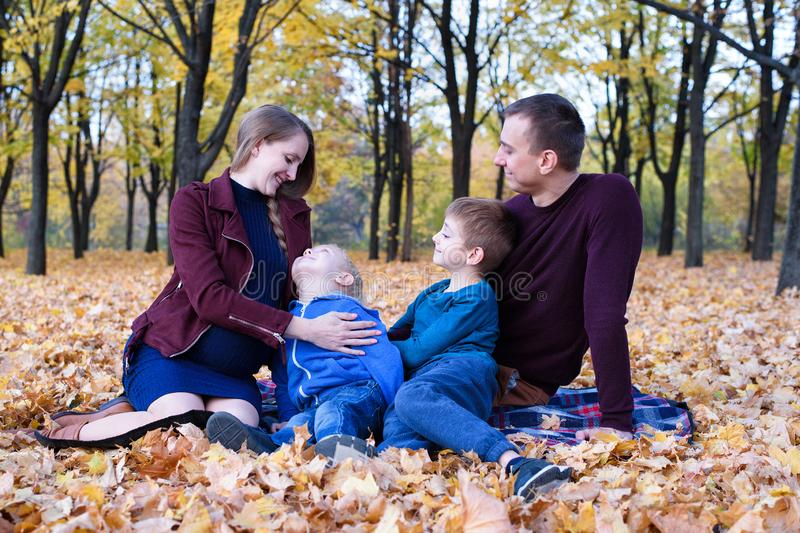 Parents and two sons relax and chat in the park. Pregnant mom Happy family. Yellow autumn foliage, sunny day stock image
