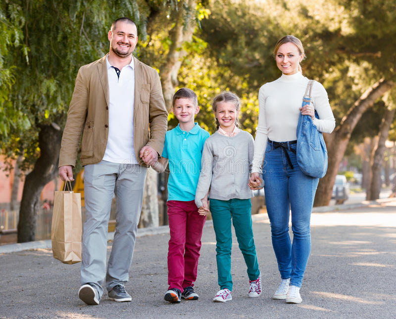 Parents with two teenagers going for shopping outdoors. Positive smiling parents with two teenagers going for a shopping outdoors stock photo