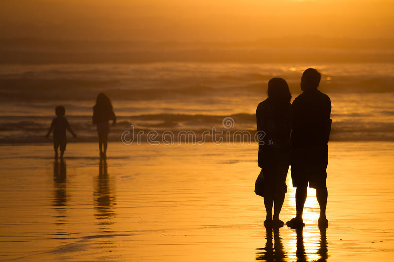 Parents watching kids silhouettes at sunset on beach stock images