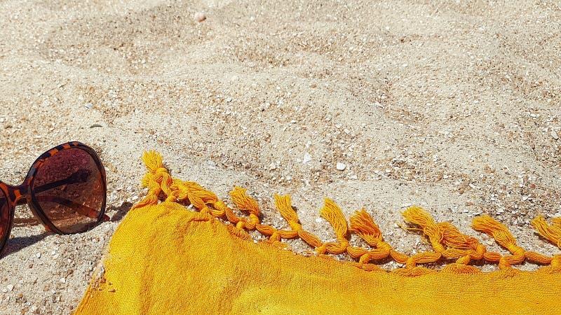 Pareo och glasögon från solen ligger på sanden arkivbild