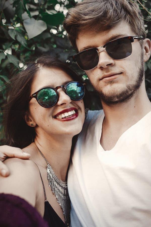 Pares à moda do moderno nos óculos de sol que sorriem e que fazem o selfie fresco Pares felizes da família no amor que faz o auto fotografia de stock royalty free