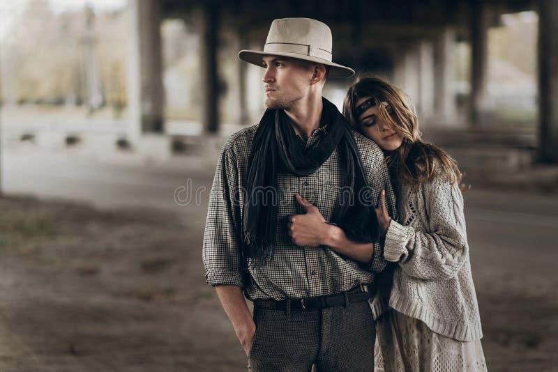 Pares à moda do moderno que abraçam delicadamente braço tocante o da mulher do boho fotos de stock