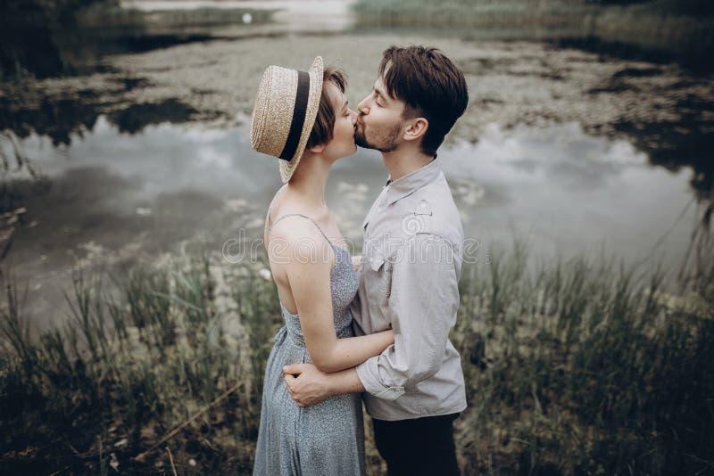 Pares à moda do moderno que abraçam no lago homem e mulher em moderno fotografia de stock royalty free