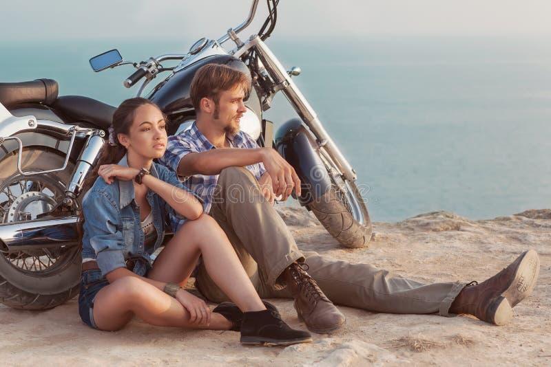 Pares à moda em uma motocicleta foto de stock