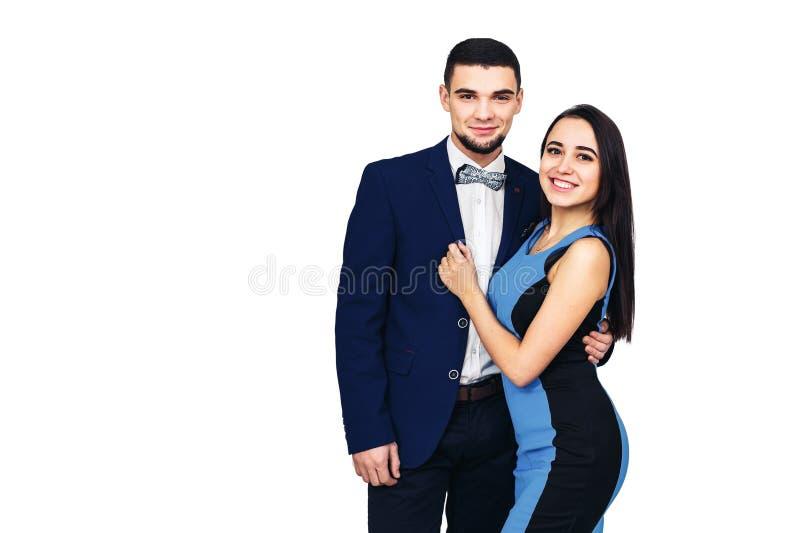Pares à moda felizes novos na roupa azul que levanta no fundo branco imagem de stock royalty free