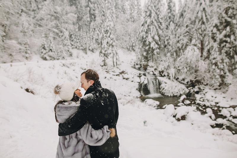 Pares à moda que abraçam em montanhas nevados do inverno Romant feliz fotos de stock