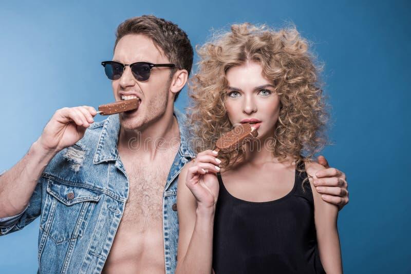 Pares à moda que comem o gelado no azul fotos de stock royalty free