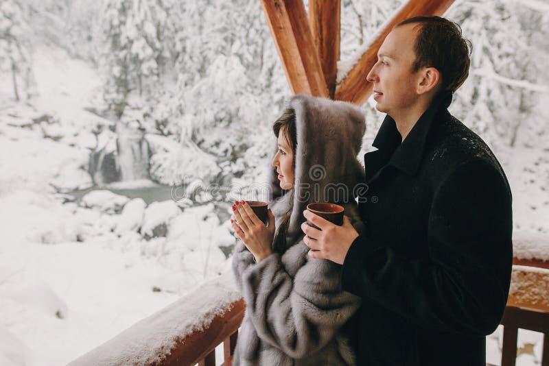 Pares à moda que guardam o chá quente em uns copos e que olham o sno do inverno fotografia de stock royalty free