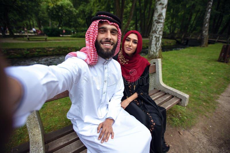 Pares árabes bonitos novos ocasionais e hijab, Abaya, tomando um selfie no gramado no parque do verão fotos de stock