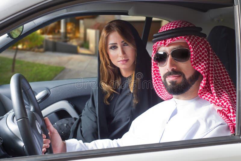 Pares árabes en un coche newely comprado foto de archivo