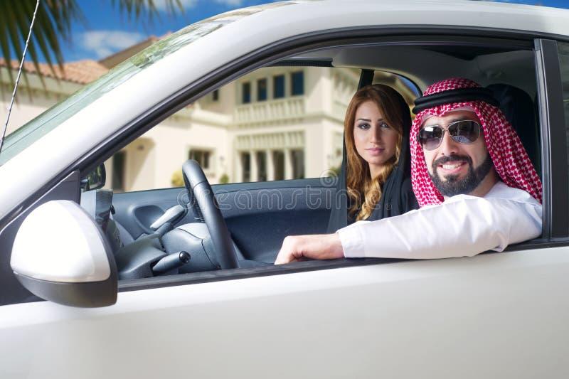 Pares árabes en un coche newely comprado imagenes de archivo