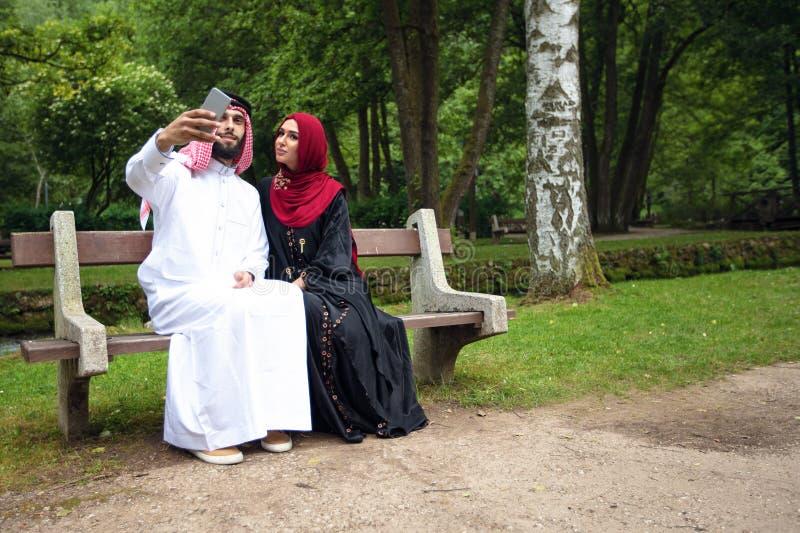 Pares árabes hermosos jovenes casuales e hijab, Abaya, tomando un selfie en el césped en parque del verano foto de archivo