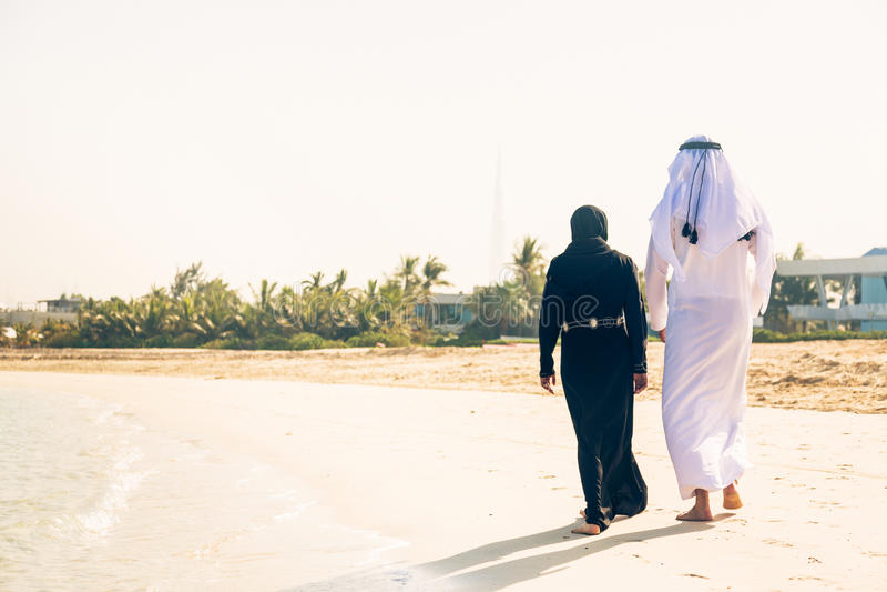 Pares árabes que andam na praia foto de stock
