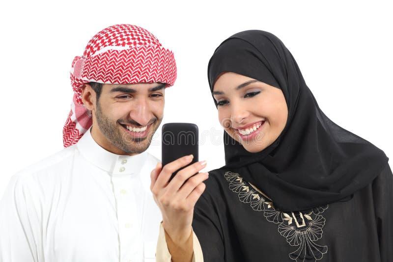 Pares árabes que comparten medios sociales en el teléfono elegante imagenes de archivo
