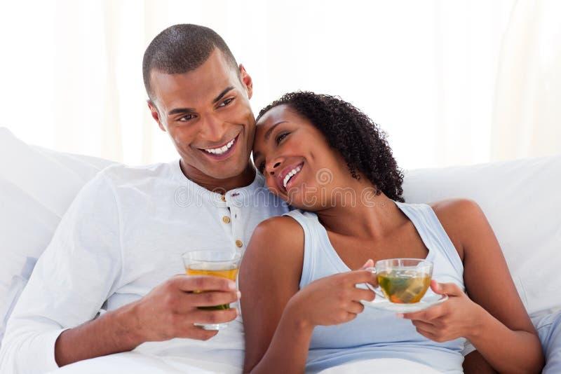 Pares étnicos felizes que bebem um copo do chá fotos de stock