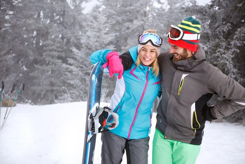Pares abrazados en pares abrazados jóvenes de esquí fotos de archivo