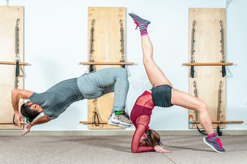 Pares acrobáticos de la aptitud joven de la yoga que se divierten en el gimnasio que realiza y que practica el foco selectivo del foto de archivo libre de regalías