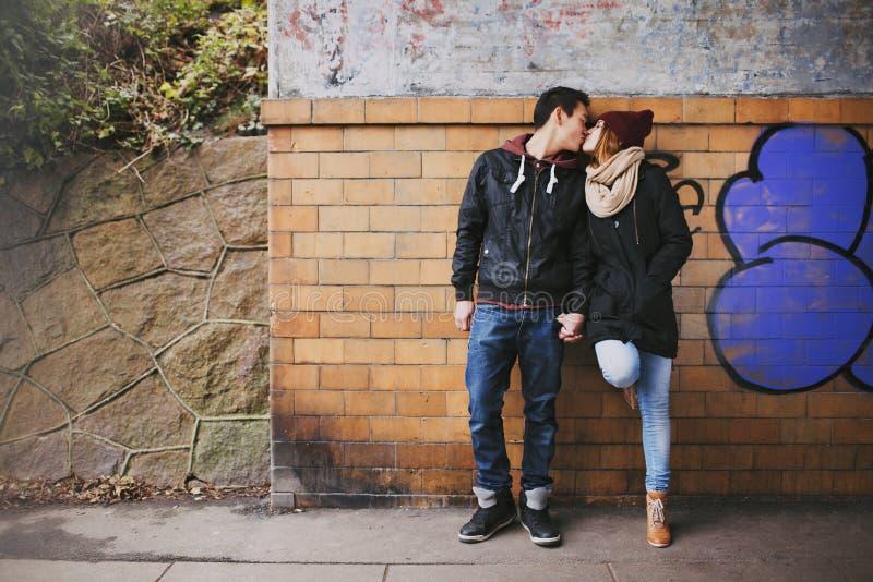Pares adolescentes afetuosos que beijam na rua imagens de stock