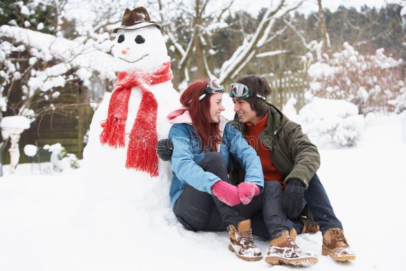 Pares adolescentes ao lado do boneco de neve com bebida quente fotografia de stock