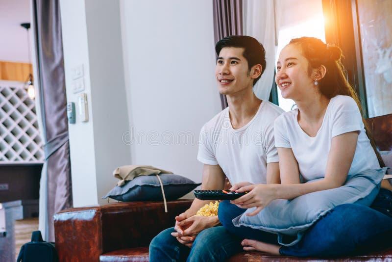 Pares adolescentes asiáticos que olham a tevê junto felizmente imagem de stock