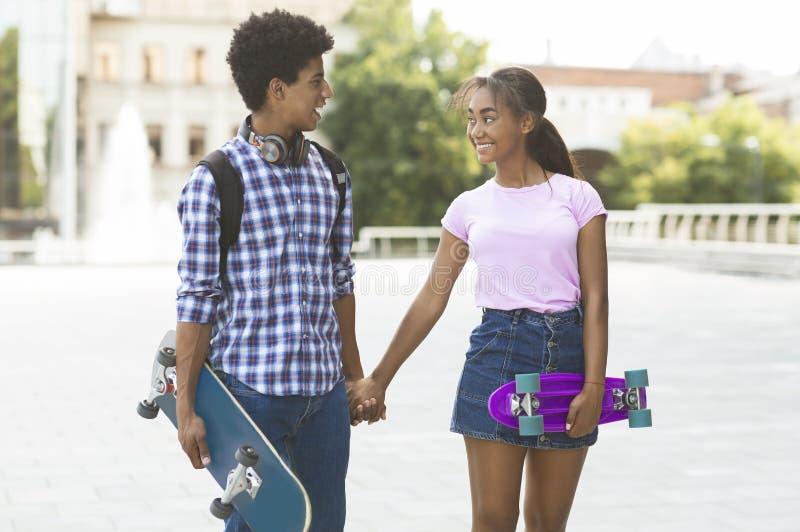 Pares adolescentes com os skates que guardam as mãos que andam ao longo da rua da cidade imagem de stock royalty free