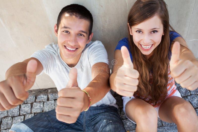Pares adolescentes com polegares acima