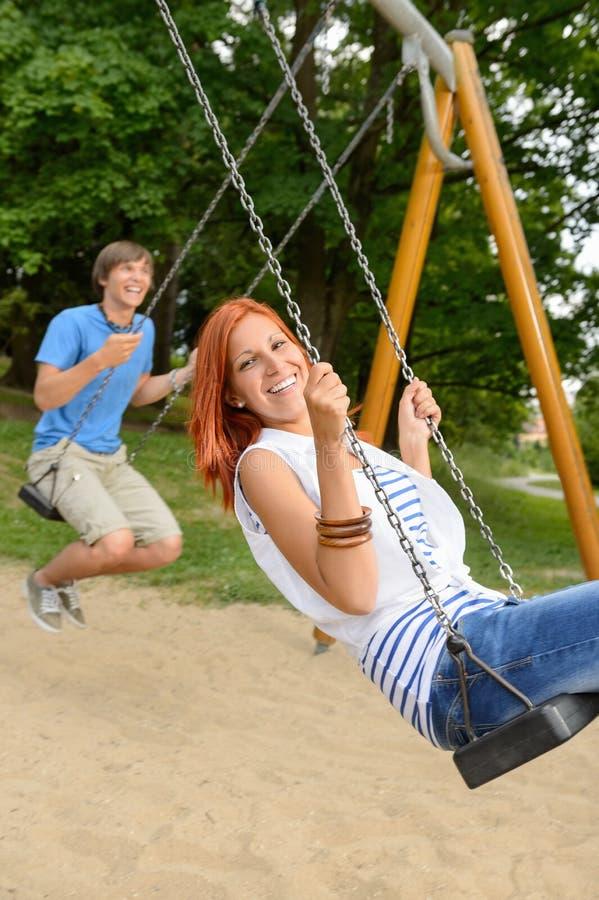 Pares adolescentes de riso no balanço no parque fotografia de stock royalty free