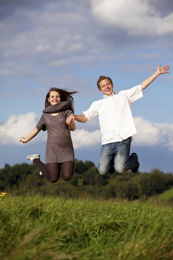 Pares adolescentes de salto felizes fotos de stock royalty free