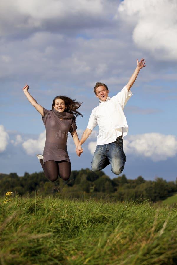 Pares adolescentes de salto felizes imagem de stock royalty free