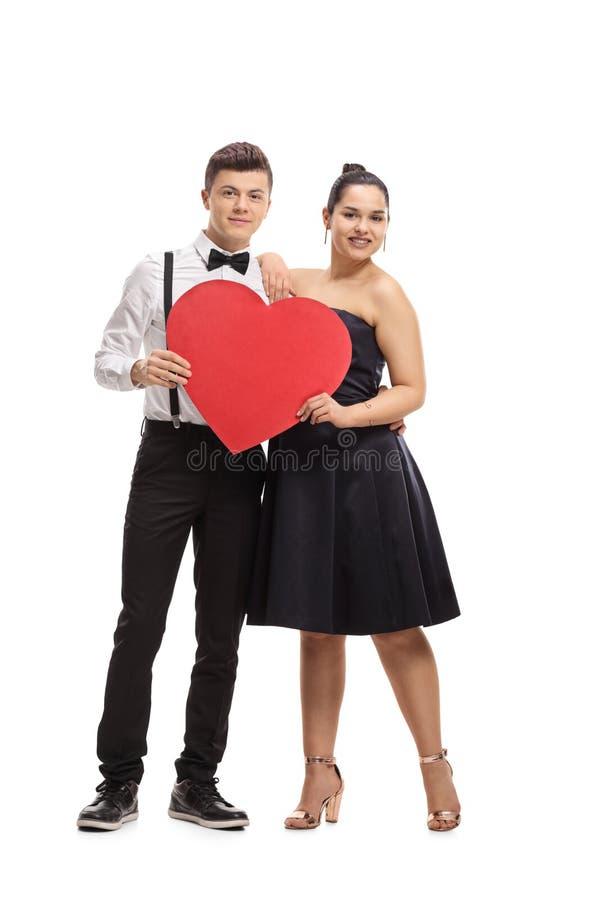 Pares adolescentes elegantemente vestidos com um coração imagens de stock