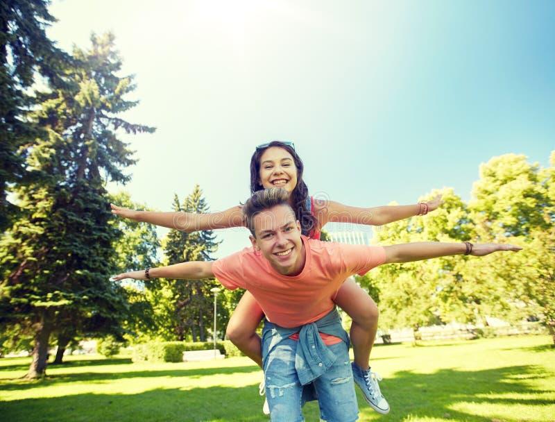 Pares adolescentes felices que se divierten en el parque del verano fotos de archivo libres de regalías