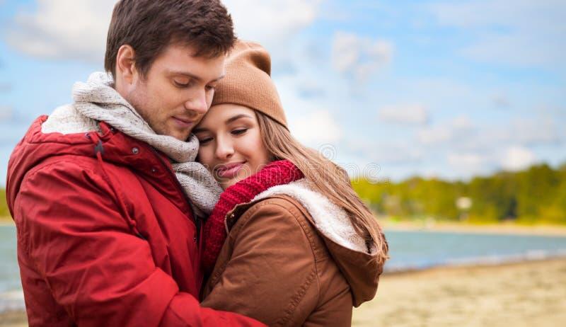 Pares adolescentes felizes que abraçam sobre a praia do outono fotografia de stock royalty free