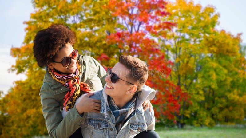 Pares adolescentes felizes que têm o divertimento no parque do outono imagem de stock