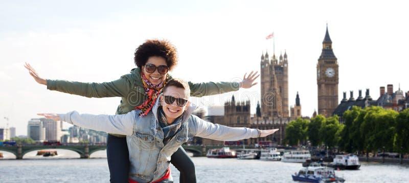 Pares adolescentes felizes que têm o divertimento sobre a cidade de Londres fotos de stock royalty free