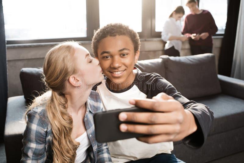 Pares adolescentes felizes que tomam o selfie com os amigos que estão atrás fotos de stock