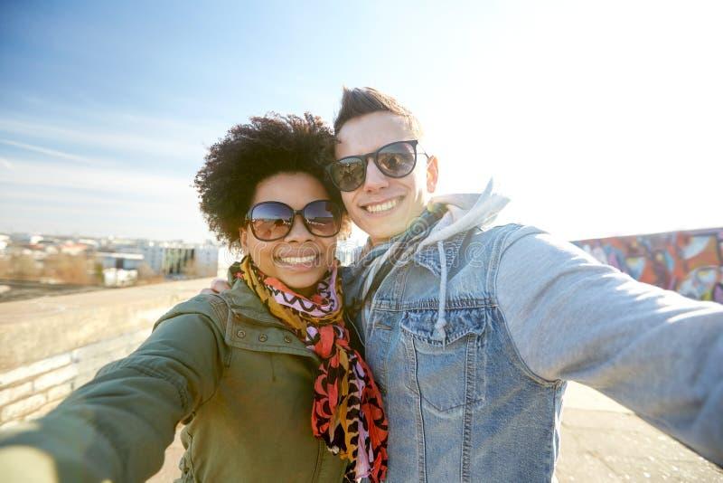 Pares adolescentes felizes que tomam o selfie na rua da cidade fotos de stock