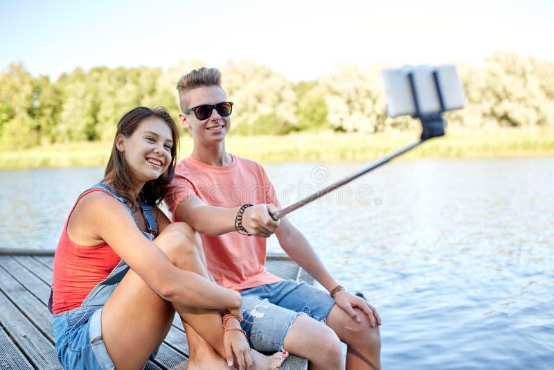 Pares adolescentes felizes que tomam o selfie no smartphone foto de stock royalty free