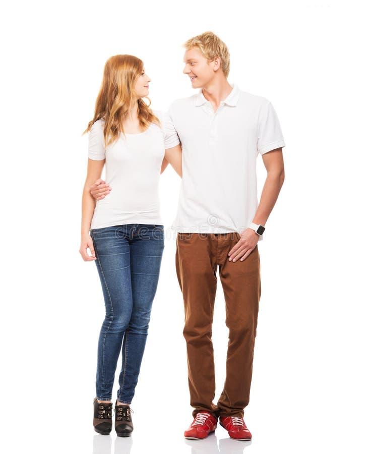Pares adolescentes novos e felizes na roupa à moda no branco imagens de stock royalty free