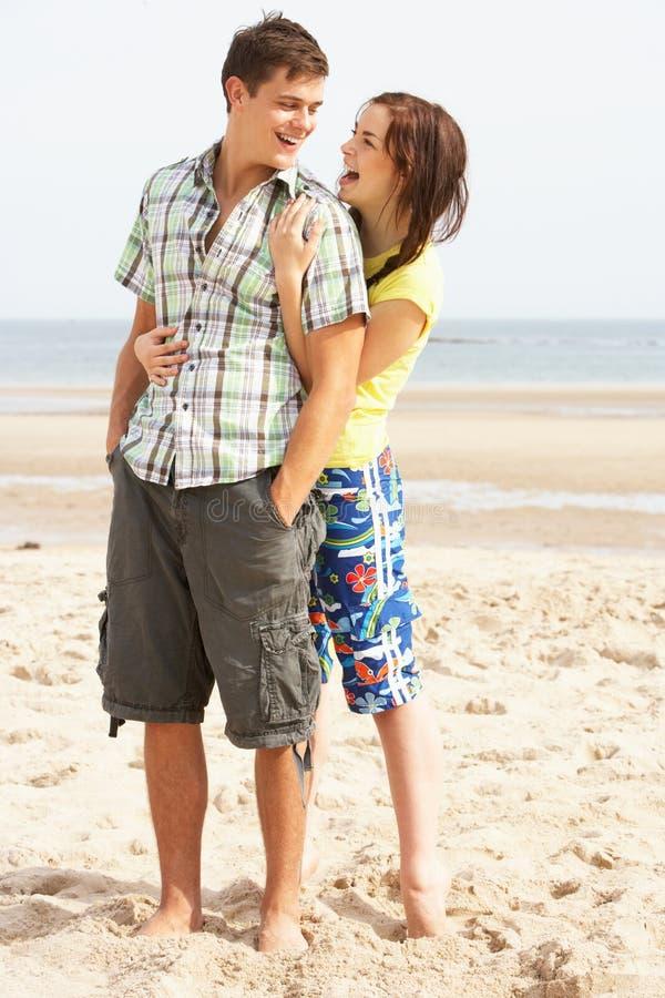 Pares adolescentes que abraçam na praia imagens de stock