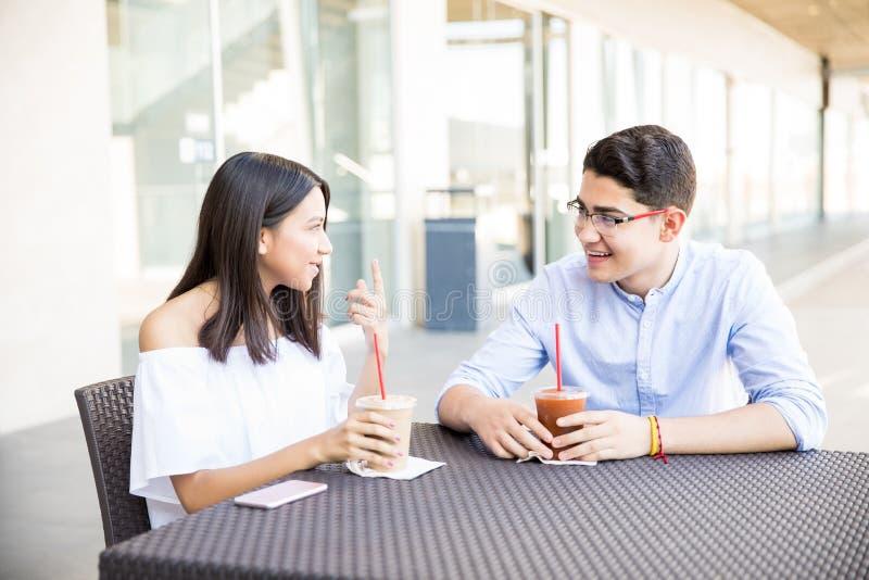 Pares adolescentes que falam ao ter bebidas no shopping imagem de stock