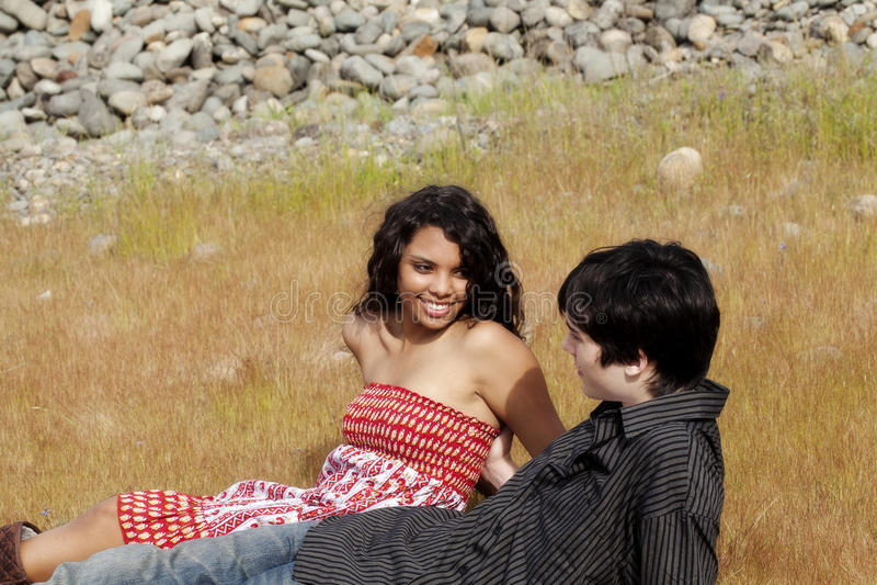 Pares adolescentes que se sientan en hierba al aire libre junto fotos de archivo libres de regalías