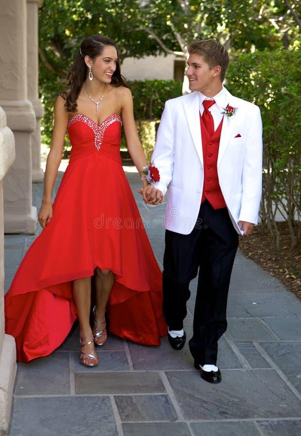 Pares adolescentes que vão ao baile de finalistas que anda e que sorri em se imagens de stock royalty free